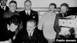 Ministrul de externe sovietic Viaceslav Molotov semenază pactul de neagresiune dintre Uniunea Sovietică şi Germania nazistă. În spatele lui se află Ribbentrop şi Stalin, 23 august 1939.