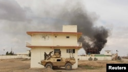 Smoke billows from a building after a Taliban attack in Helmand province March, 2016
