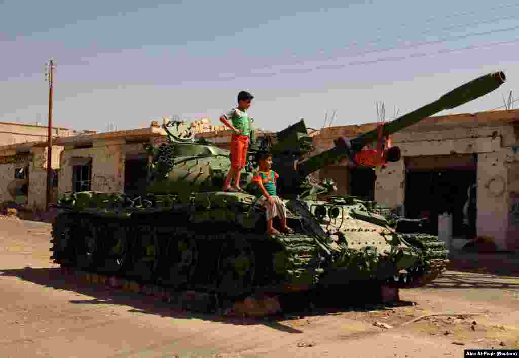 Boys play on a damaged military tank that belonged to forces loyal to Syrian President Bashar al-Assad in the rebel-held southern town of Bosra al-Sham, is Syria's Deraa Governorate, on September 19. (Reuters/Alaa al-Faqir)