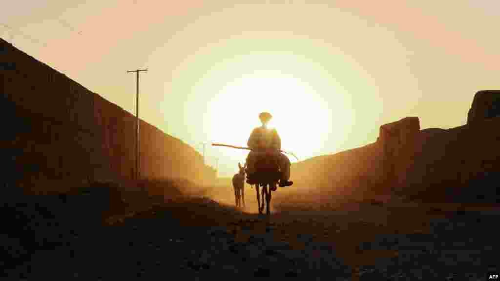 An Afghan villager rides a donkey in a dusty road in the Zadyan district of Balkh Province on September 23. (AFP/Qais Usyan)