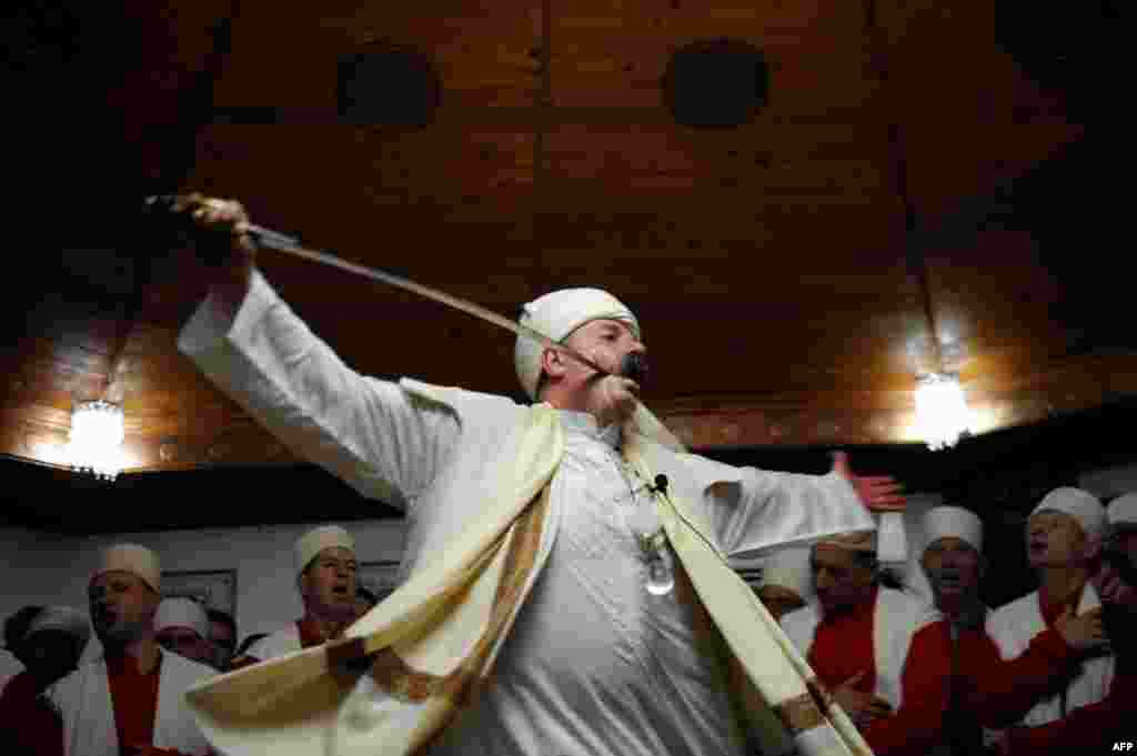 Kosovar dervishes, adepts of Sufism, a mystical form of Islam that preaches tolerance and a search for understanding, take part in a ceremony in the prayer room in the town of Gjakova. (AFP/Armend Nimani)