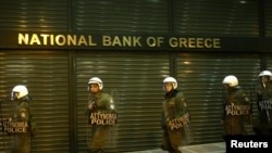 Riot policemen secure a bank branch during an antigovernment rally in Athens last month, fueled by the economic crisis.
