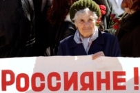 A woman holds a sign saying \