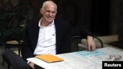 Грчкиот премиер во заминување Јоргос Папандреу седи во кафуле во близина на парламентот во Атина на 8 ноември 2011 година.
