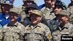 Президент Казахстана Нурсултан Назарбаев (в центре) после военного парада по случаю Дня защитника Отечества на военном полигоне Отар. Жамбылская область, 7 мая 2013 года.