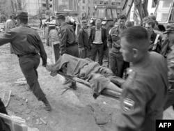 Спасатели несут тело одной из жертв взрыва в Волгодонске 16 сентября 1999 года