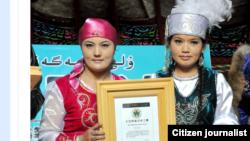 Гиннестер рекордына енді деп хабарланған Алтай шайына берілген сертификатты ұстап тұрған қазақ қыздар. Сурет Алтай аймақтық әкімдігінің ресми сайтынан алынды