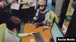 Dressed in an outfit vaguely reminiscent of Robocop, the former economy and trade minister glided through the flagship Sberbank branch in Moscow wearing special glasses, earmuffs, and body padding designed to impair his sight and hearing, and restrict his movement.