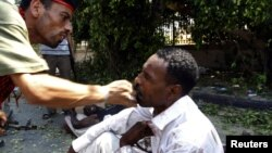 A Libyan rebel combatant slaps a wounded man accused of fighting for Muammar Qaddafi