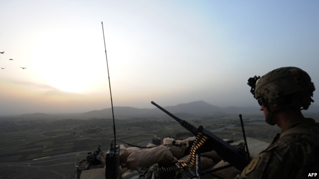 A U.S. soldier stands guard on a watch tower overlooking villages at Combat Outpost Sabari in the Khost Province in June