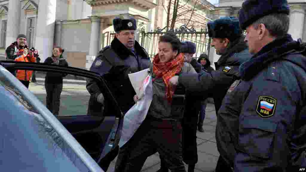 Police officers detain a gay-rights activist who tried to protest against antigay legislation in St. Petersburg on April 6, 2012.