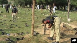 A police officers collects evidence at the site of a suicide bombing in Lower Dir in September 2011. (file photo)