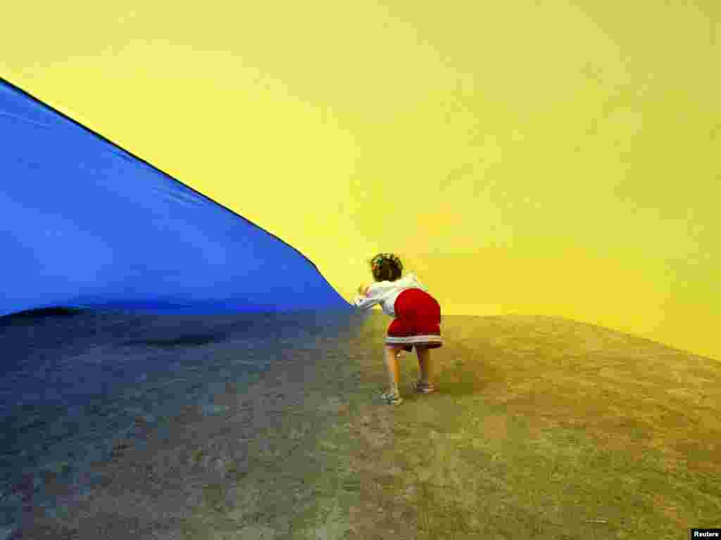 A girl walks under a giant Ukrainian national flag, held by people celebrating the Day of the State Flag in Kyiv on August 23.Photo by Konstantin Chernichkin for Reuters