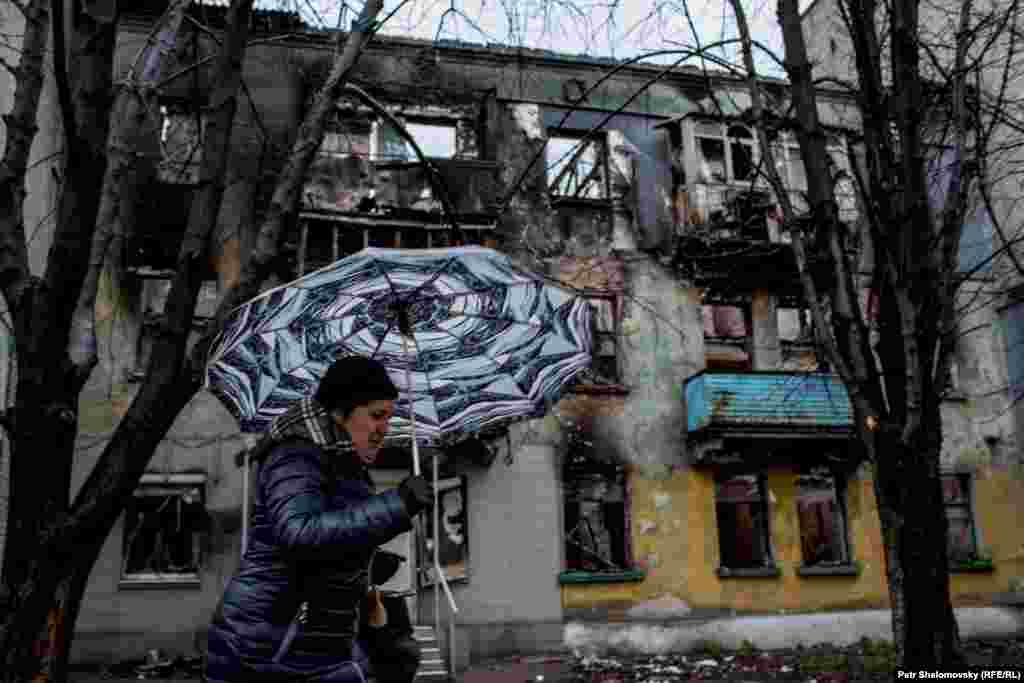 A woman walks past a destroyed building in Debaltseve.