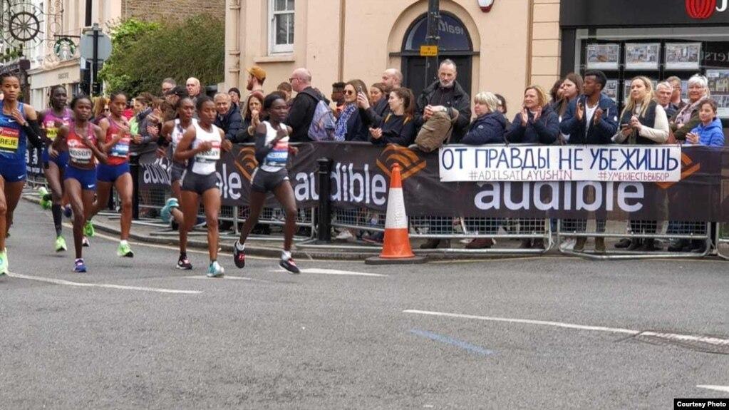 """Баннер с надписью: """"От правды не убежишь"""" — вдоль маршрута Лондонского марафона. 28 апреля 2019 года."""