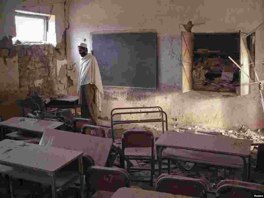 A man walks through a destroyed classroom of a boys' school hit by a bomb in Landikotal in northwest Pakistan. Unidentified men planted the bomb, which resulted in no casualties. (REUTERS/Shahid Shinwari)