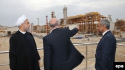 Iranian President Hassan Rohani (left) and Iranian Oil Minister Bijan Namdar Zangeneh (center) attend the inauguration of a new gas phase at the South Pars gas field near the southern Iranian port of Assalouyeh on March 17. Iran has likely lost billions in revenue from oil and natural gas due to sanctions over the last few years.
