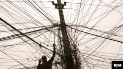 An electrician checks the wires leading to a block of flats in Baghdad's Karrada district
