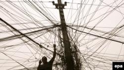 عامل كهرباء يتفحّص أسلاك تجهيز الكهرباء من مولدة في الكرادة ببغداد