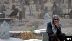 """A man at Kabul's graveyard for Afghan """"martyrs"""" in the fight against Soviet troops in September 2006"""