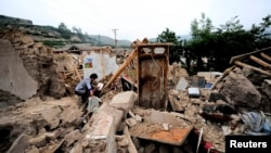 China -- A woman is seen on ruins of a damaged house after a 6.6 magnitude earthquake hit Minxian county, Dingxi, Gansu province, July 23, 2013