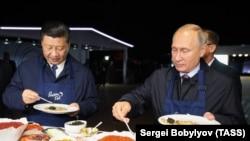 Президент Китая Си Цзиньпин и президент России Владимир Путин с тарелками с блинами и икрой во время Восточного экономического форума на острове Русский.