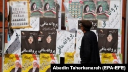 An Iranian man looks at electoral posters and fliers during the last day of election campaign, in Tehran, February 19, 2020