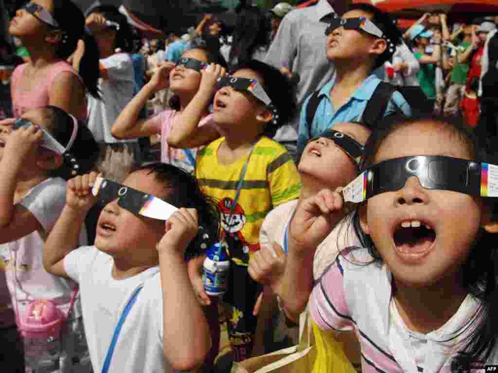 Тайвань. Дети наблюдают за самым долгим солнечным затмением в 21 веке.