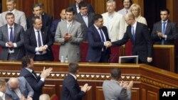 Премьер-министр Украины Арсений Яценюк (справа) получает поздравления депутатов Верховной Рады после решения не принимать его прошение об отставке. Киев, 31 июля 2014 года.