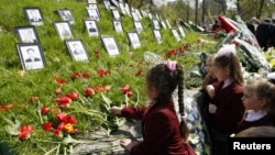 Fëmijët vendosin lule në monumentin e viktimave të Çernobilit në Kijev në 26 vjetorin e katastrofës