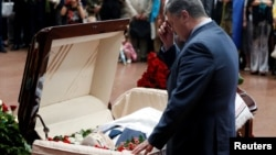 "Ukrainian President Petro Poroshenko reflects at the coffin of journalist Pavel Sheremet, who was killed by a car bomb on July 20 in Kyiv. While condemning attacks on journalists, Poroshenko has also said journalists should not write ""negative articles"" about Ukraine."