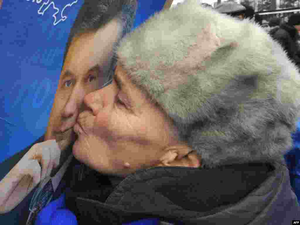 A Viktor Yanukovych supporter kisses his portrait during a rally in Kyiv.