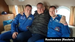 Roskosmos chief Dmitry Rogozin (center) poses with Russian cosmonaut Aleksei Ovchinin (left) and U.S. astronaut Nick Hague after their emergency landing.