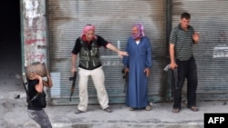 Syria -- A Syrian rebel carries a homemade explosive device as others stand back to let him pass during clashes with government troops in the Salhin district of the northern city of Aleppo on 31Jul2012
