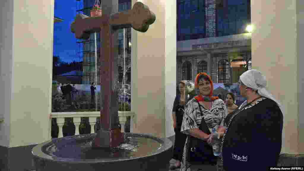 Женщины стоят около святого источника на территории монастыря. Для встречи иконы люди приезжали из отдаленных районов Алматы.