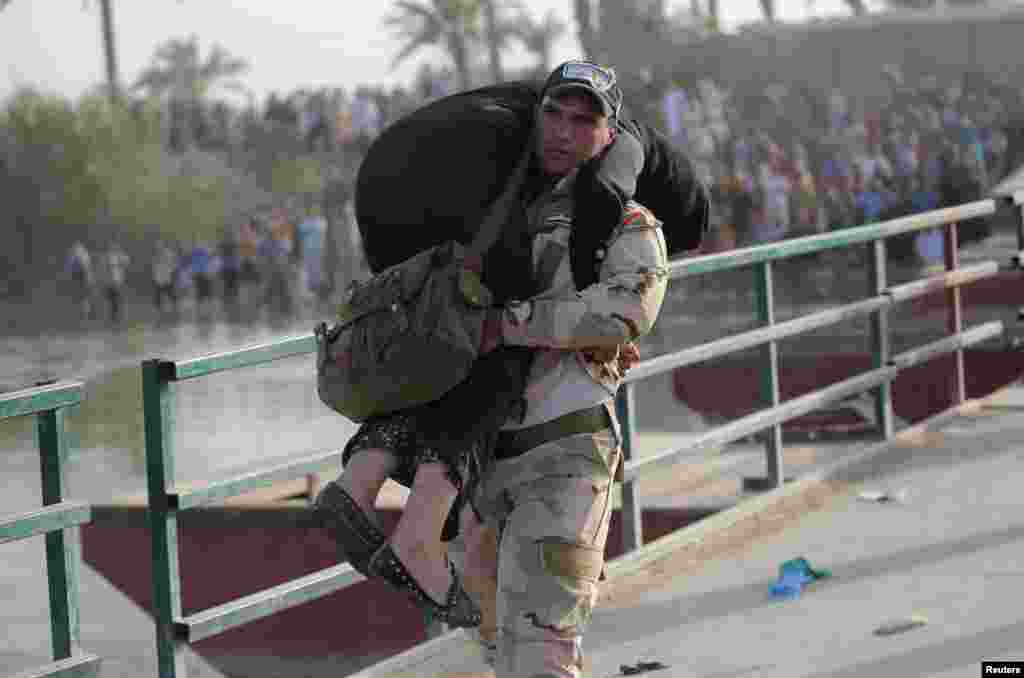 An Iraqi soldier helps a displaced woman cross a bridge at the outskirts of Baghdad. (Reuters/Stringer)