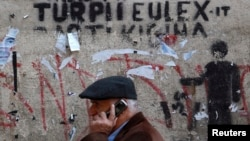 """A man walks past a wall in Pristina with graffiti that reads, """"The shame of EULEX."""""""