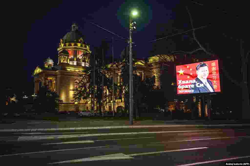 """Un ecran pe care este afișat mesajul """"mulțumesc"""" adresat președintelui chinez Xi Jinping, lângă clădirea Adunării Naționale a Serbiei. La sfârșitul lunii aprilie, un înalt oficial al UE a spus: """"Dacă ați putea merge la Belgrad, ați vedea panouri publicitare pe străzile principale ale Belgradului, cu mesajul: << Mulțumesc frate Xi, sunteți singurul care ne ajută.>> Ceea ce este foarte amuzant, pentru că nu am văzut niciodată un panou publicitar care să spună """"Mulțumesc UE pentru ajutorul oferit. Și am oferit mult ajutor Serbiei și altor țări din Balcani."""""""