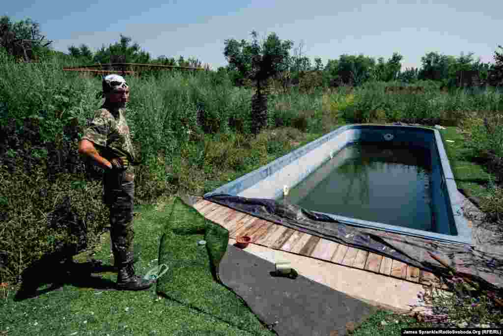 A soldier nicknamed Wolf checks out a dirty swimming pool at a mansion in Pisky.