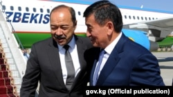 Uzbek Prime Minister Abdulla Aripov (left) is greeted by Kyrgyz Prime Minister Sooronbai Jeenbekov at Manas airport in Bishkek on August 16.