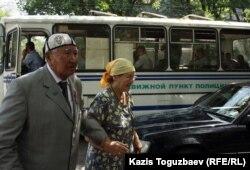 Казахский писатель Сапабек Асип с женой, на заднем плане - автобус с полицейскими. Алматы, 31 мая 2012 года.