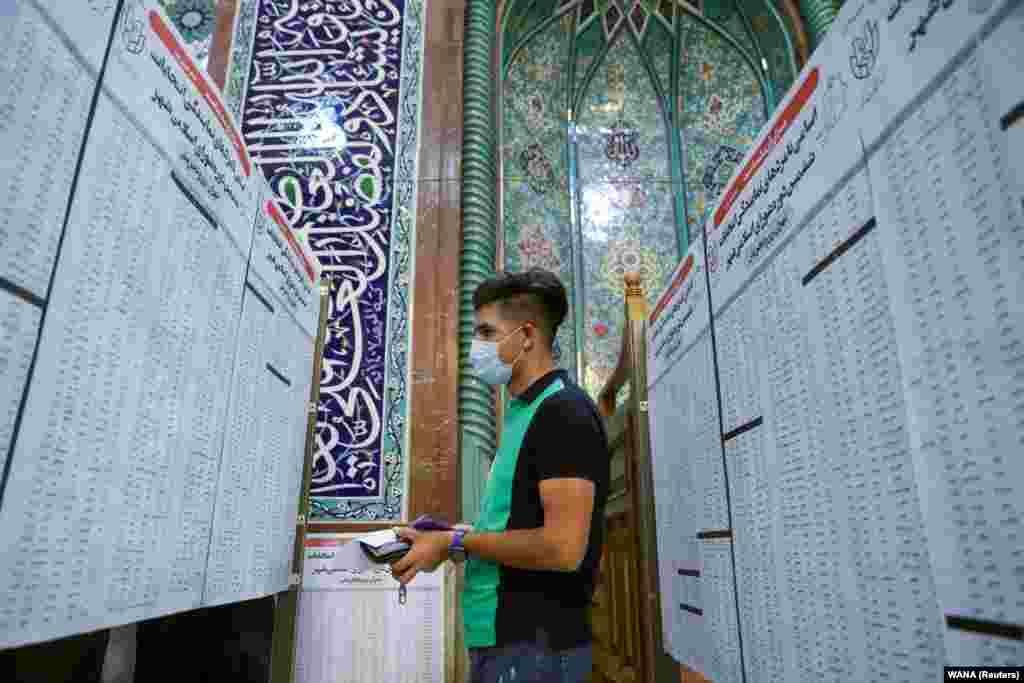 Član biračkog mjesta provjerava spiskove ljudi na biralištu, Teheran (18. juni)