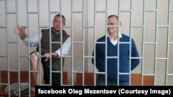Ukrainian citizens Mykola Karpyuk (right) and Stanislav Klyh (left) in a defendants' cage in a court in Grozny.