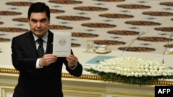 Turkmen President Gurbanguly Berdymukhammedov holds up his credentials during his inauguration ceremony as president in Ashgabat on February 17.