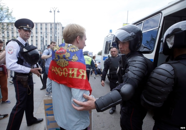 Russian police officers detain a participant at an opposition rally on Tverskaya Street in central Moscow on June 12.