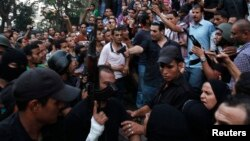عناصر أمنية مصرية بلباس مدني يرافقون موالون لجماعة الأخوان المسلمين وسط موالين للحكومة الإنتقالية