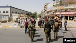 Iraqi security forces gather at the site of a suicide bomb blast in Baghdad al-Jadida on September 27.