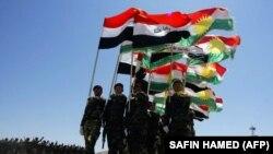 پیشمرگههای کرد عراق در حال رژه با پرچم اقلیم و پرچم عراق؛ ائتلاف به رهبری آمریکا در جریان نبرد با گروه حکومت اسلامی با اقلیم کردستان و دولت مرکزی عراق همکاری میکند