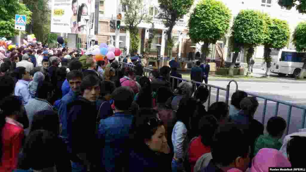 Собравшиеся в центре Алматы стоят за ограждением.