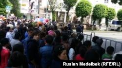 Собравшиеся в центре Алматы на празднование Дня единства народа стоят за ограждением. 1 мая 2016 года.